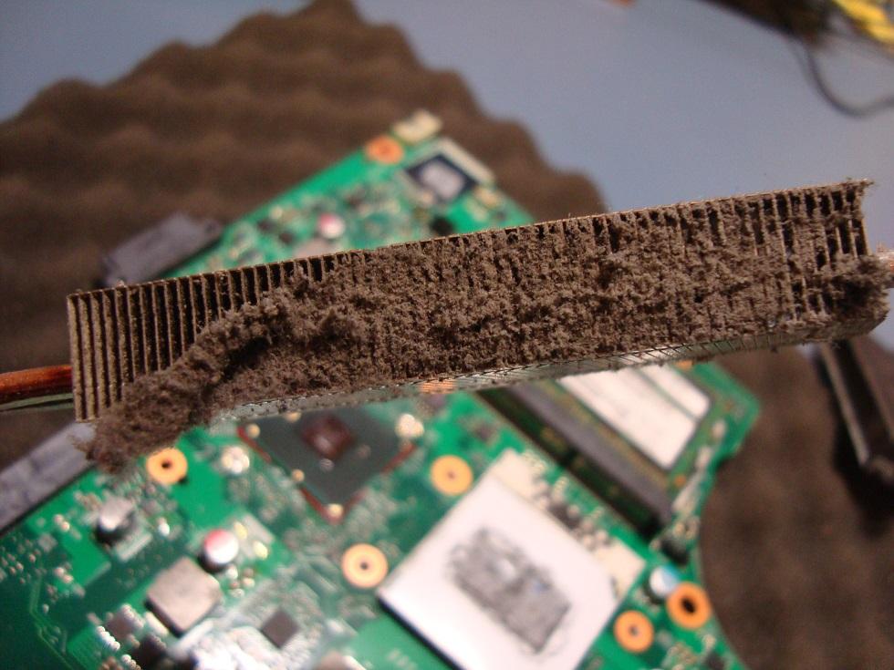 Detailní pohled na zanesené žebrování chladiče uvnitř notebooku